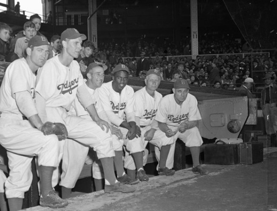 """Members of the Brooklyn Dodgers and their new coach pose in front of their dugout before an exhibition game with the New York Yankees. The team has a new manager and new Negro star player from Montreal, Jackie Robinson."""
